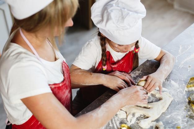 Moeder en dochter hebben plezier met het bereiden van koekjes met melk aan een eettafel in een gezellige keuken