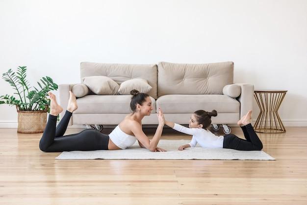 Moeder en dochter hebben plezier met spelen en sporten thuis op de vloer