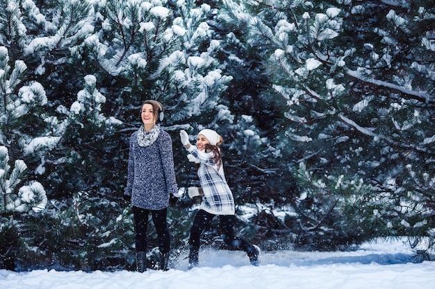 Moeder en dochter hebben plezier met spelen in het winterbos