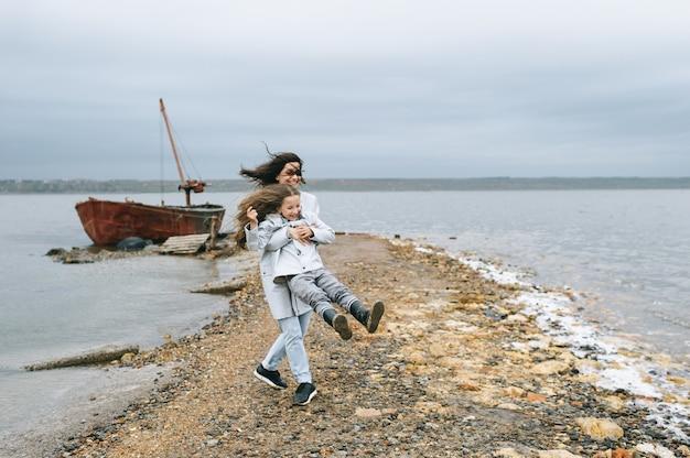Moeder en dochter hebben plezier op de achtergrond van een boot in de buurt van het meer