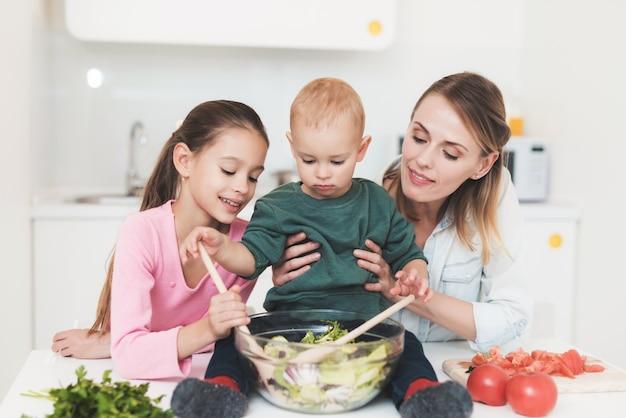 Moeder en dochter hebben plezier tijdens het bereiden van een salade