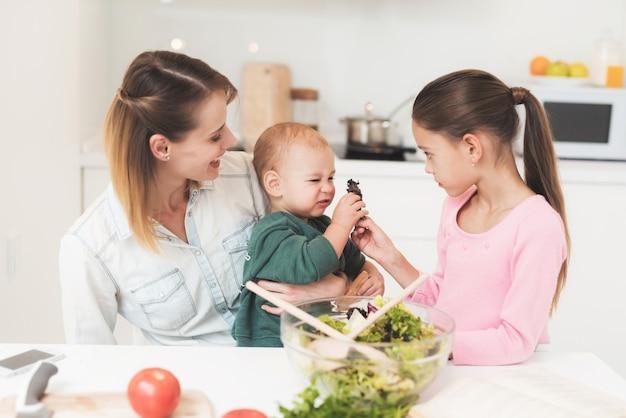 Moeder en dochter hebben plezier tijdens het bereiden van een salade.