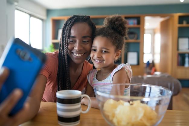 Moeder en dochter hebben samen plezier en nemen een selfie met mobiele telefoon terwijl ze thuis blijven. monoparentaal concept. nieuw normaal levensstijlconcept.