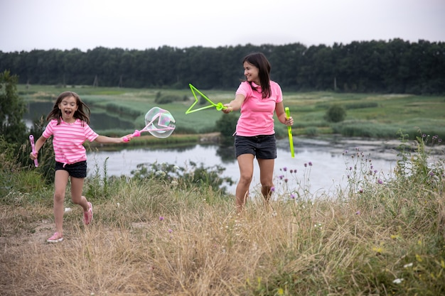 Moeder en dochter hebben samen plezier, maken grote zeepbellen, actieve gezinsrecreatie in de buitenlucht.
