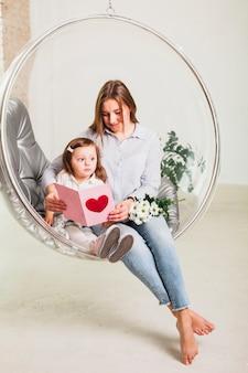 Moeder en dochter het lezen van wenskaart in hangende stoel