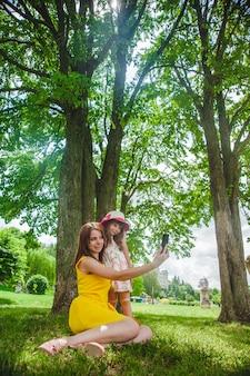 Moeder en dochter het nemen van een auto-foto in een park
