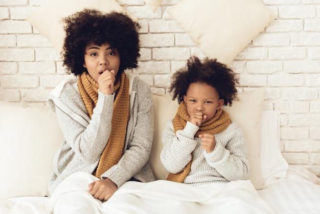 Moeder en dochter hoesten zittend op bed thuis.
