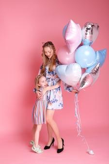 Moeder en dochter houden ballonnen tegen roze oppervlak. moederdag Premium Foto