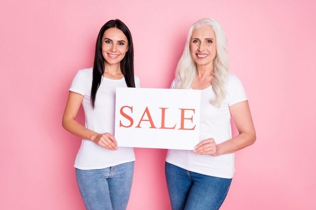 Moeder en dochter houden banner met verkoop