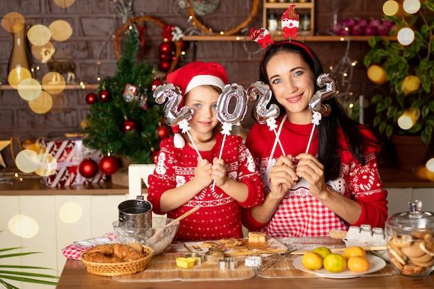 Moeder en dochter houden de nummers 2022 vast in een donkere keuken met een kerstboom en koken gemberkoekjes voor nieuwjaar of kerstmis, glimlachen en hebben samen plezier in afwachting van de vakantie