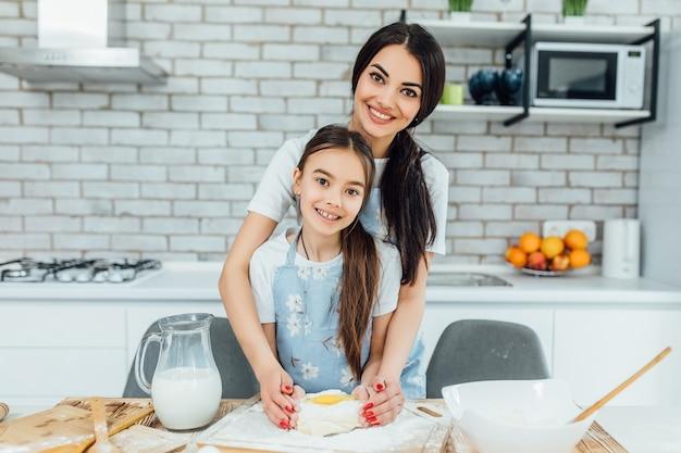 Moeder en dochter houden dienblad met ongebakken koekjes samen in de keuken