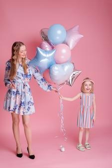 Moeder en dochter houden een bos ballonnen tegen een roze oppervlak. familie