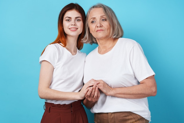 Moeder en dochter houden elkaars hand vast in witte tshirts familie samen