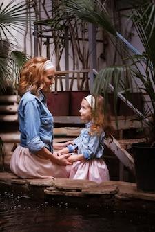 Moeder en dochter houden elkaars hand vast, kijken elkaar aan en glimlachen. lief en zacht uiterlijk. blonde moeder en dochtertje in roze rokken en denim shirts houden hun handen buiten op hun riem