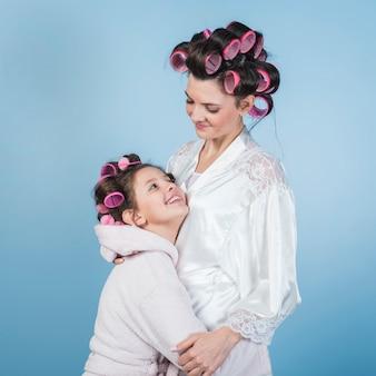 Moeder en dochter in badjassen en krulspelden knuffelen