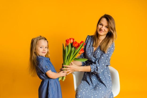 Moeder en dochter in blauwe jurken met een boeket rode tulpen op een gele muur