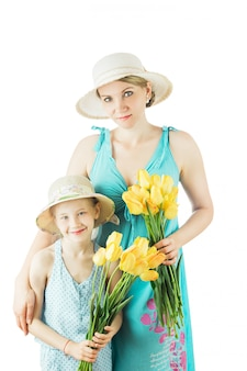 Moeder en dochter in blauwe kleding en hoeden die op witte achtergrond wordt geïsoleerd.