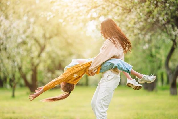 Moeder en dochter in bloeiende kersentuin