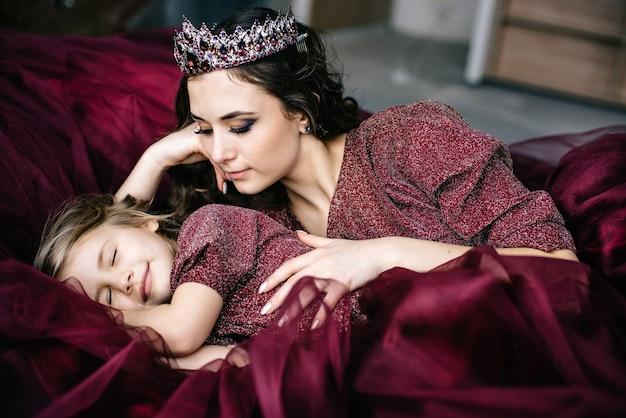 Moeder en dochter in de afbeelding van de koningin en prinses jurken kleur marsala liggen samen in bed, close-up, selectieve aandacht