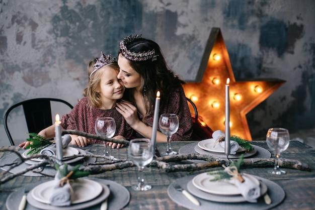 Moeder en dochter in de afbeelding van de koningin en prinsessenjurken in de kleuren van marsala de kersttafel