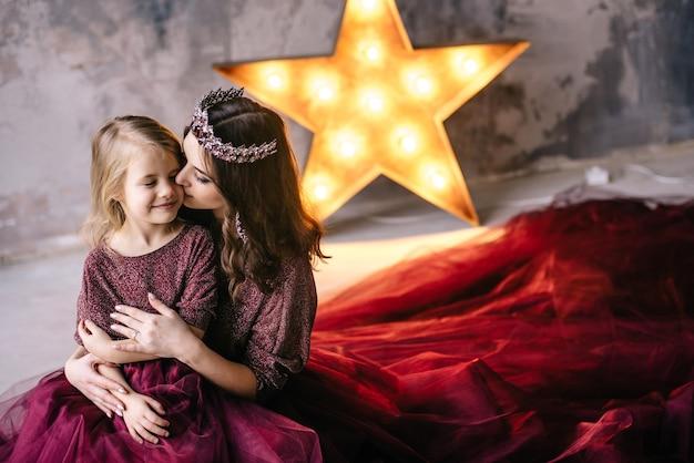 Moeder en dochter in de afbeelding van de koningin en prinsessenjurken in de kleuren van marsala met een lange trein op het hok