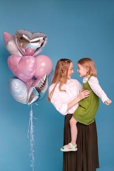 Moeder en dochter in de buurt van ballonnen op een blauw oppervlak