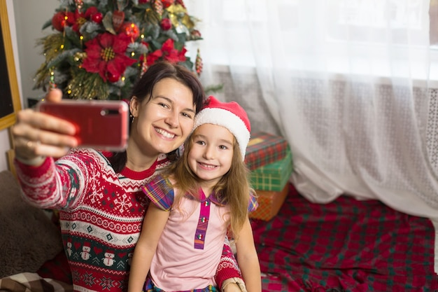 Moeder en dochter in de buurt van de kerstboom, foto's en selfies maken aan de telefoon