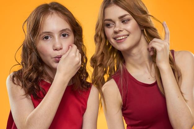 Moeder en dochter in de gele levensstijl van het rode jurkenentertainment
