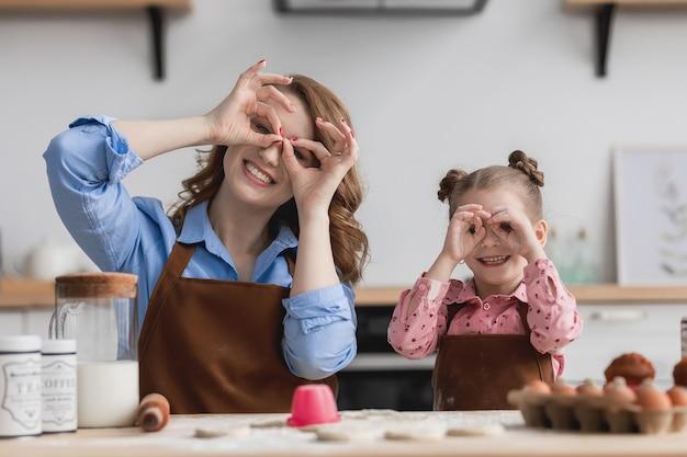 Moeder en dochter in de keuken aan de keukentafel trekken gezichten