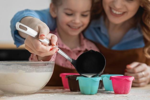 Moeder en dochter in de keuken hebben plezier en koken eten van meelmelk en eieren
