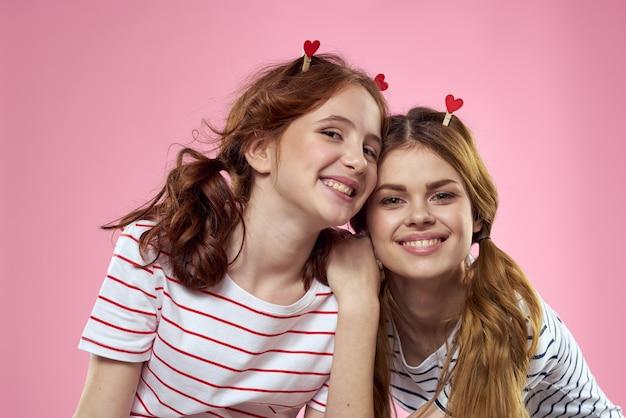 Moeder en dochter in de studio poseren veel plezier en glimlach, gelukkige familie, twee zussen, harten en roze achtergrond