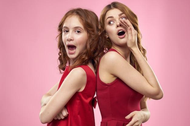 Moeder en dochter in de studio poseren veel plezier en glimlach, gelukkige familie, twee zussen