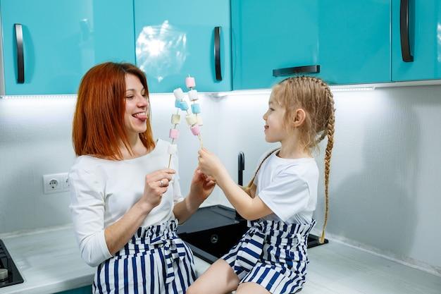 Moeder en dochter in de turquoise keuken spelen met marshmallows. mooie familierelaties. gelukkig familieconcept