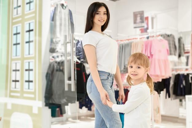Moeder en dochter in de winkel met kleding voor kinderen.