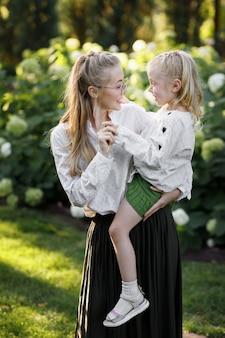 Moeder en dochter in de zomer op een wandeling in het park op een groene achtergrond