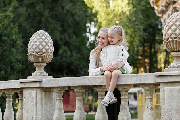 Moeder en dochter in de zomer op een wandeling in het park