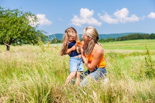 Moeder en dochter in de zomer op weide