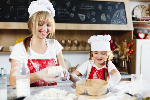 Moeder en dochter in dezelfde kleding hebben plezier bij het bereiden van een deeg in een gezellige keuken