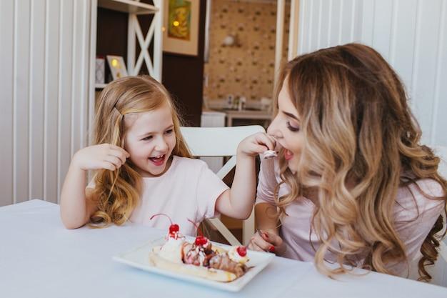 Moeder en dochter in een café zitten aan een tafel en voeden elkaar ijs Premium Foto