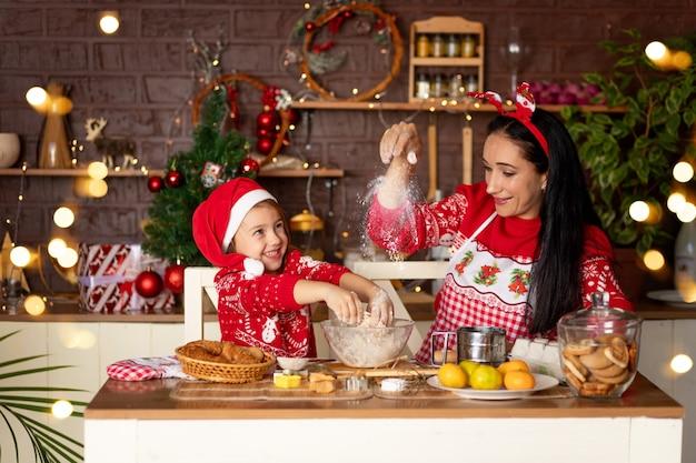 Moeder en dochter in een donkere keuken met een kerstboom bereiden gemberkoekjes voor nieuwjaar of kerstmis, glimlachen en hebben samen plezier in afwachting van de vakantie in een kerstmanhoed