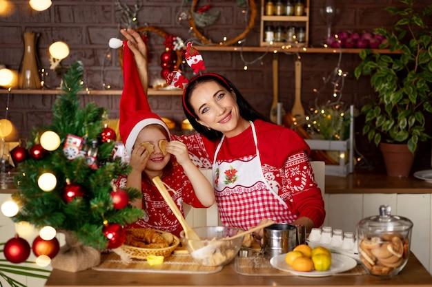 Moeder en dochter in een donkere keuken met een kerstboom bereiden gemberkoekjes voor nieuwjaar of kerstmis, glimlachend en gek rond in een kerstmanhoed