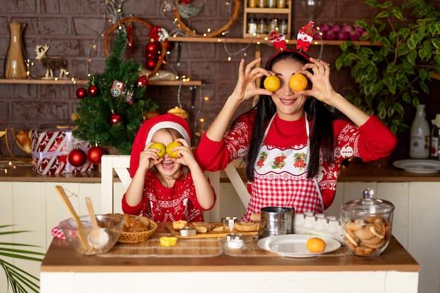 Moeder en dochter in een donkere keuken met een kerstboom bereiden gemberkoekjes voor nieuwjaar of kerstmis, glimlachend en gek rond met mandarijnen in een kerstmanhoed