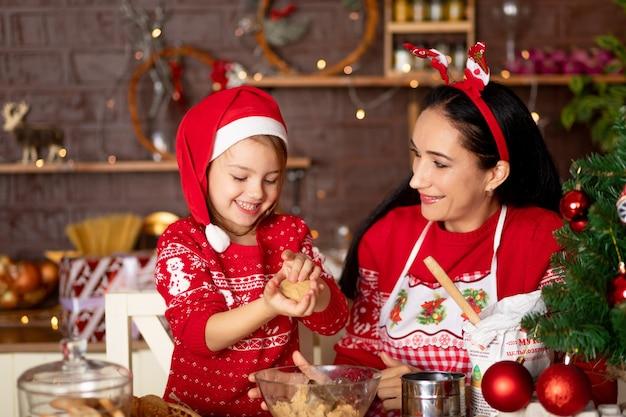 Moeder en dochter in een donkere keuken met een kerstboom koken gemberkoekjes voor het nieuwe jaar of kerstmis en glimlachen in een kerstmanhoed