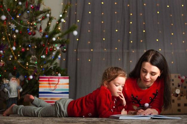 Moeder en dochter in een rode trui voor kerstmis bij de kerstboom. blijf thuis tijdens de vakantie.