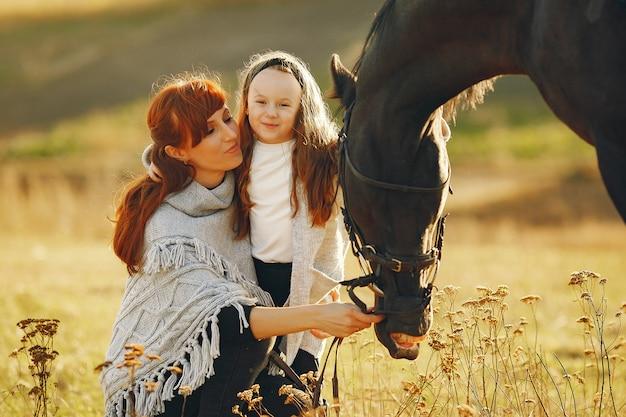 Moeder en dochter in een veld spelen met een paard