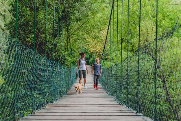 Moeder en dochter in het bos die over houten brug lopen