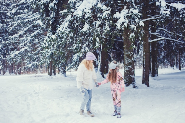 Moeder en dochter in het bos van de winter