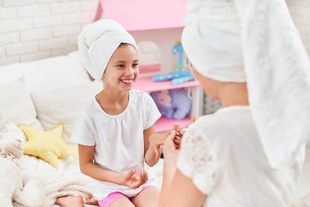 Moeder en dochter in huiskleren en handdoeken op hun hoofd doen manicure