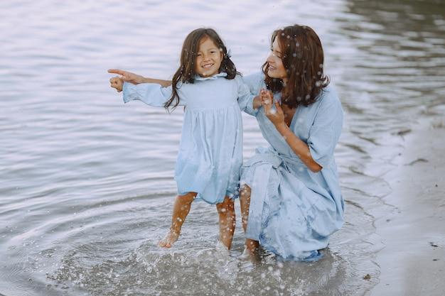 Moeder en dochter in identieke jurken. familie spelen bij de rivier.
