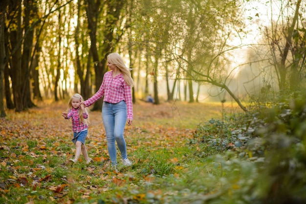 Moeder en dochter in jeans en roze shirts lopen in de herfst park.